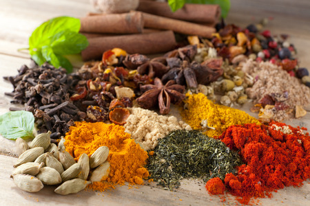 green herbs: Closeup of an assortment of colorful spices, herbs and teas on a wooden table