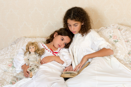 bedtime: Vintage girl in bed reading a bedtime story to her little sister