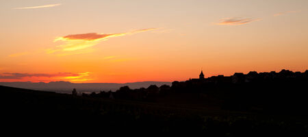 Sunrise of the French Alsace region with village silhouette photo