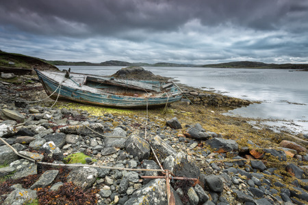 Weathered fishing boat lying on a rocky beach on the Isle of Lewis, Outer Hebrides, Scotland photo