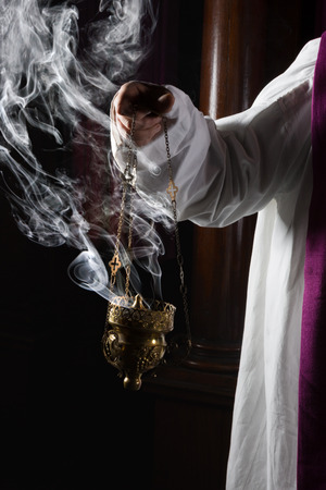 roman catholic: Church incense burner held by a catholic priest