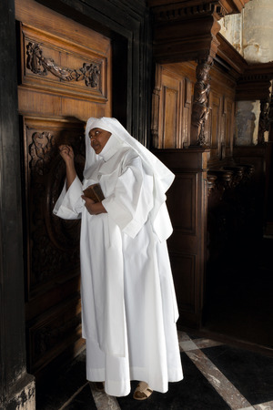 Nun knocking on the vicars door in a medieval church Stock Photo