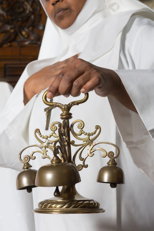 catholic mass: Church bells rung by a nun during the consecration of catholic mass