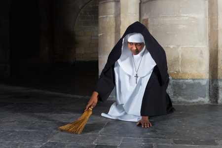 convent: Nun sweeping the floor of a medieval abbey with a hand brush