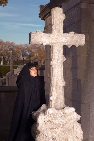 Victorian woman praying at All Saints in a graveyard photo