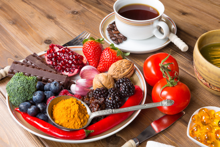 Wooden table filled with antioxidant drinks and food Standard-Bild