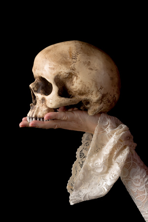 creepy hand: Creepy human skull held by a female hand wearing antique lace sleeves