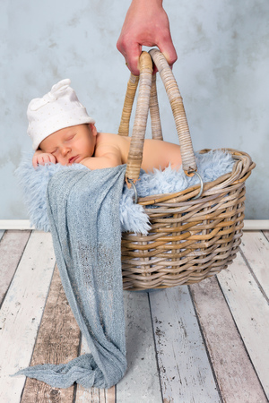 adorable seven days old newborn baby boy in a wicker basket stock