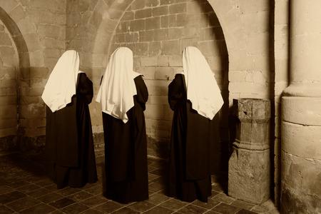 Drie nonnen in gewoonte staan in een middeleeuwse abdij Stockfoto