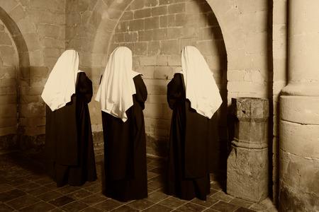 Three nuns in habit standing in a medieval abbey Stock Photo
