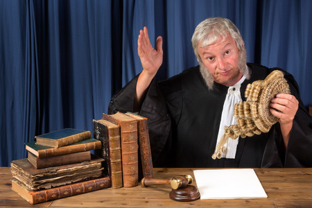 Mature judge taking his wig off in court
