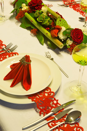 Christmas table decorated with red napkins and flower arrangement photo
