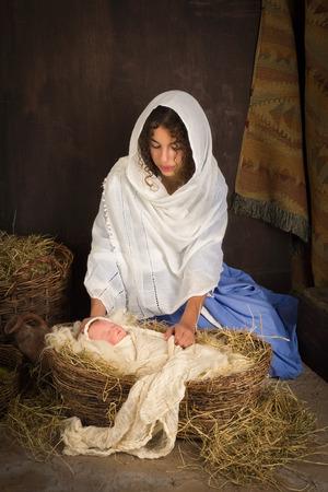 ティーンエイ ジャーの女の子がライブ クリスマスのキリスト降誕のシーンの人形と聖母マリアの役割を果たして