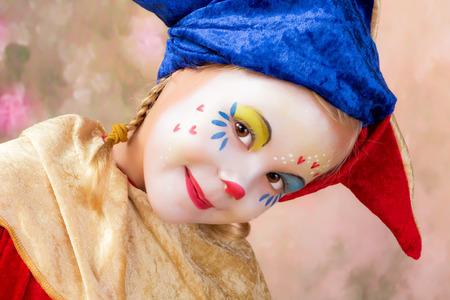 Lovely little clown girl with blond braids