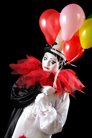 Unhappy female Pierrot clown holding colorful balloons  photo