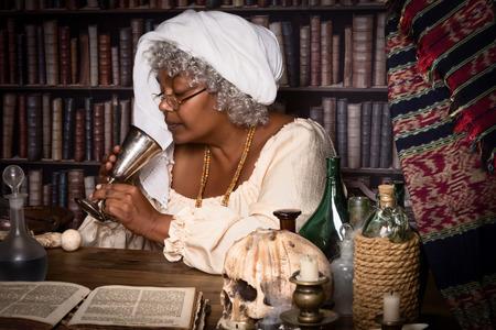 poison bottle: Dark alchemist tasting a brew from her laboratory