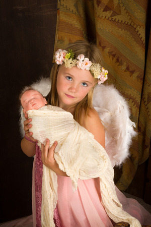 Pink little girl playing an angel in a Christmas nativity scene with a doll photo