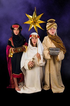 reyes magos: WISEMEN interpretado por tres chicas en una escena viva de la natividad de la Navidad Foto de archivo