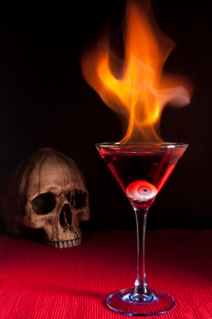 Burning halloween cocktail with skull and glass eye Stock Photo