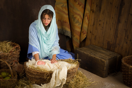 nascita di gesu: Giovane ragazza giocando il ruolo della Vergine Maria con una bambola in una scena dal vivo presepe di Natale Archivio Fotografico