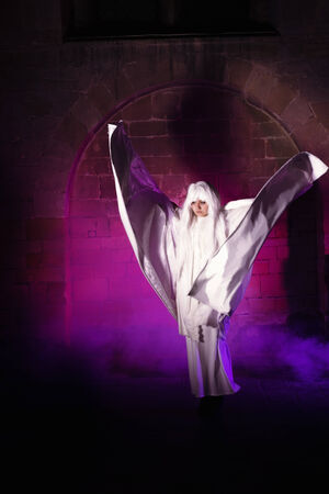 White ghost with long hair roaming around in a medieval castle photo