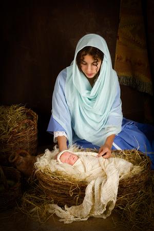 virgen maria: Chica adolescente jugando el papel de la Virgen Mar�a con una mu�eca en una escena viva de la natividad de la Navidad Foto de archivo