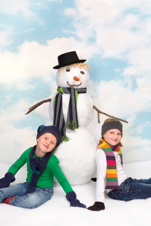 Two little sisters sitting next to their new snowman photo