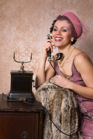 antique telephone: Stunning vintage 1920s woman talking on an antique telephone