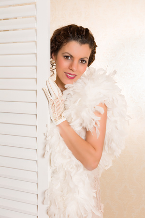 feather boa: Young brunette in vintage 1920s feather boa looking from behind a folding screen in her boudoir Stock Photo