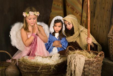 Kleine 7 jaar oude engel bezoek aan een kerststal nagespeeld met een pop Stockfoto