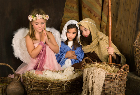 Little 7 year old angel visiting a nativity scene reenacted with a doll Stock Photo