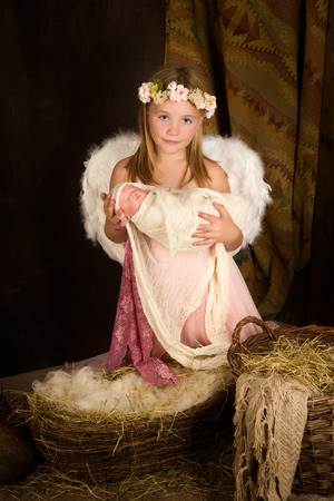 infant jesus: Pink little girl playing an angel in a Christmas nativity scene with a doll