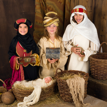 reyes magos: Tres niñas jugando como sabios con una muñeca en un pesebre de Navidad