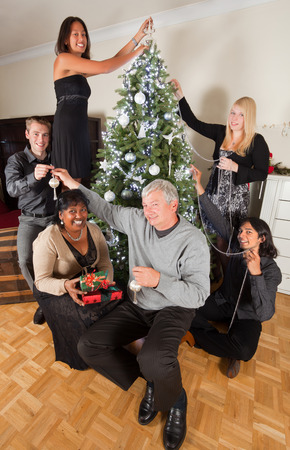 decorating christmas tree: Cheerful family decorating the christmas tree together Stock Photo