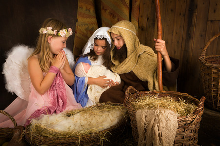 Little 7 year old angel visiting a nativity scene reenacted with a doll Stockfoto