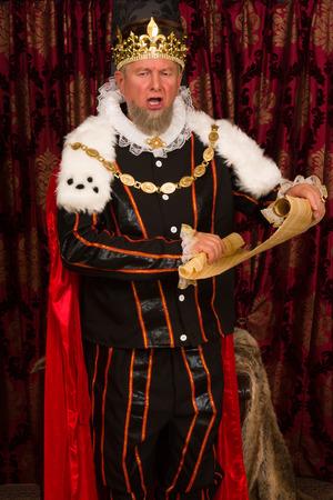 rey: Rey mayor que hace un anuncio con un rollo de pergamino Foto de archivo
