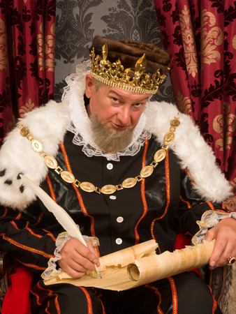 Oude koning de ondertekening van een nieuwe wet met een veer ganzenveer