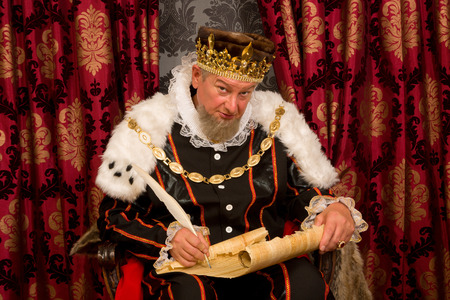 medieval scroll: Old king signing a new law with a feather quill