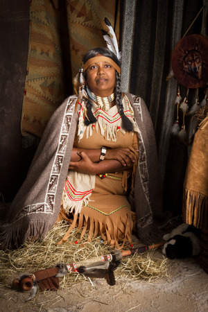 cherokee: Weathered mature tribal female storyteller talking about heroic times