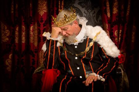 corona rey: Rey pensativo y preocupado sentado en su trono