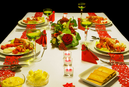 Luxury lobster and white wine on a festive table with red folded napkins photo