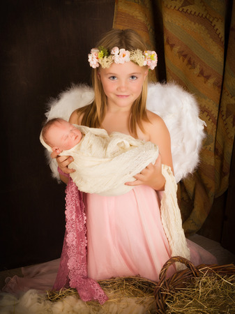 child jesus: Pink little girl playing an angel in a Christmas nativity scene with a doll