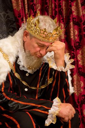 trono: Rey pensativo y preocupado sentado en su trono