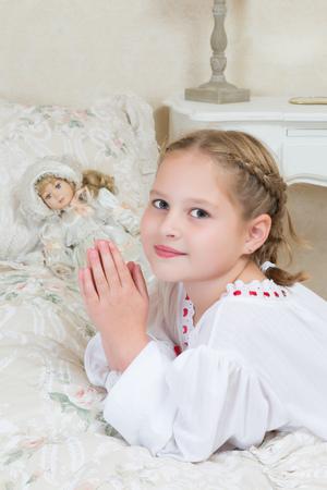 innocent girl: Innocent little girl praying in her bedroom Stock Photo