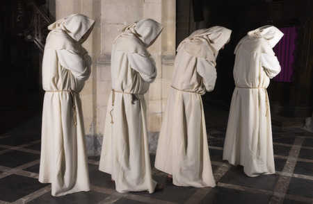 only 1 man: Four monks walking in a row along a pillar of a medieval church (composite image with only 1 man) Stock Photo