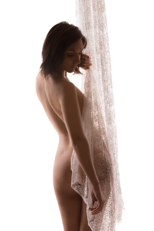 Fine art nude portrait of a young woman holding ivory lace