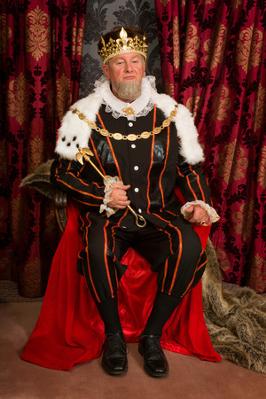 costumes: King in tudor costume sitting on his throne holding his scepter