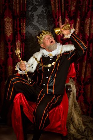 tudor: Old funny king getting drunk holding a golden goblet