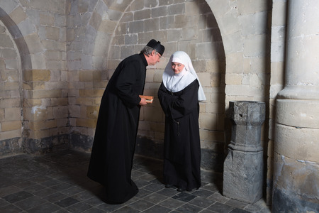 carmelite nun: Priest and nun telling gossip in the corners of a medieval church