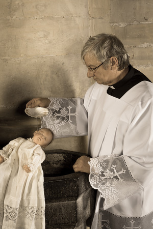 roman catholic: Sepia image of a vintage priest baptizing a baby